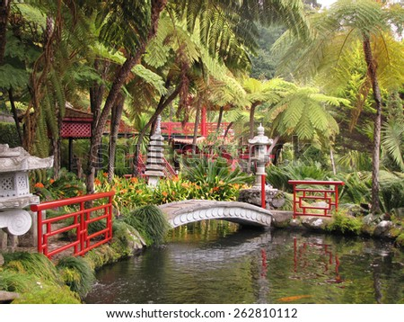 Lovely park on the island of Madeira -  Monte Palace Tropical Garden. The red Chinese-style pavilions and a wonderful bridge over a pond with goldfish - stock photo