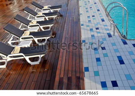 lovely pool deck and chaise lounges on luxury cruise ship - stock photo