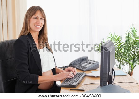 Lovely pregnant woman working with a computer at the office - stock photo