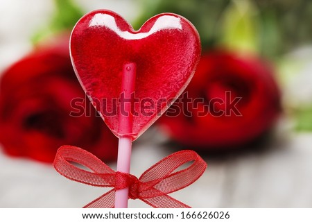 Lovely red lollipop in heart shape. Symbol of sweet love. Valentines day gift. Bouquet of roses in the background - stock photo