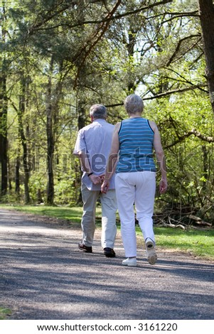 Lovely senior couple out for a walk in the woods on a summer afternoon - stock photo