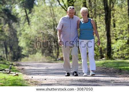 Lovely senior couple strolling through the park arm in arm - stock photo