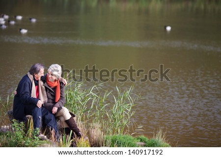 Lovely senior couple talking and looking at each other on the river side - stock photo