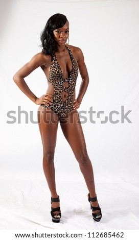 Lovely, sexy African American woman in swim suit standing with her hand on her hip