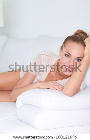 Lovely smile on beautiful elegant woman reclining on a white sofa with her head raised looking at the camera - stock photo