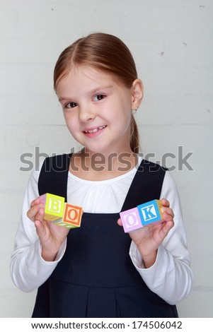 """Lovely smiling little schoolgirl holding the word """"book"""" of children's blocks/Young girl in school uniform playing with letter cubes and composes words - stock photo"""