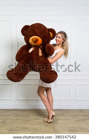 Lovely smiling young woman holding, big soft teddy bear - stock photo