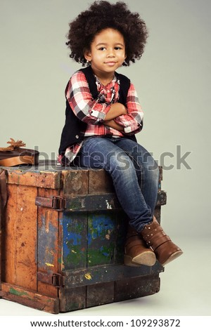 Lovely stylish little girl sitting on an old wooden box - stock photo