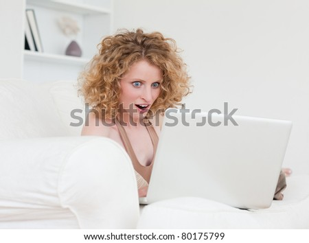 Lovely surprised female relaxing with her laptop while sitting on a sofa in her apartment - stock photo