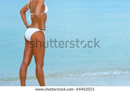 lovely tanned female blonde bikini model standing beside ocean water at florida beach - stock photo