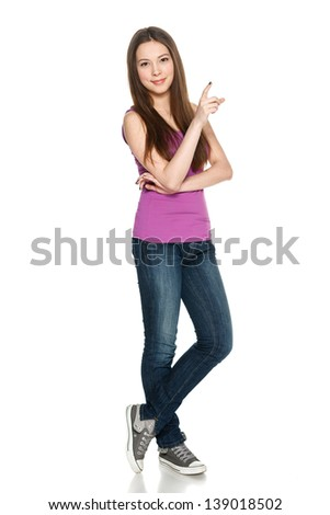 Lovely teen girl in full length standing casually and pointing to the side at blank copy space, against white background - stock photo