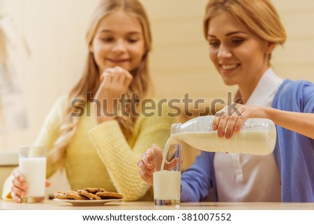 Lovely teenage girl and her beautiful mother having a bite while sitting in the kitchen. Mother pouring a milk. - stock photo