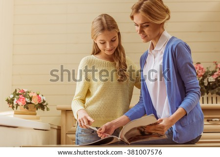 Lovely teenage girl and her beautiful mother reading a magazine and smiling while sitting at home