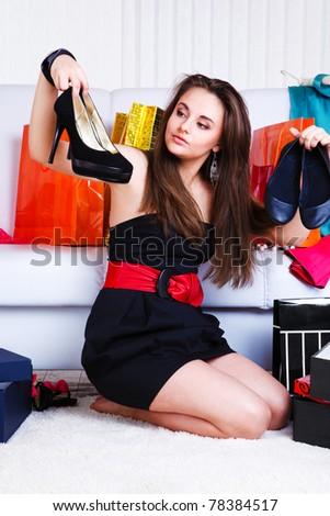 Lovely teenage girl choosing shoes - stock photo
