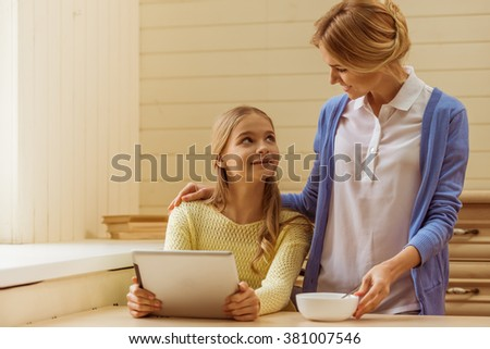 Lovely teenage girl using a tablet, beautiful mother holding a bowlful. Both looking at each other and smiling while sitting at home.