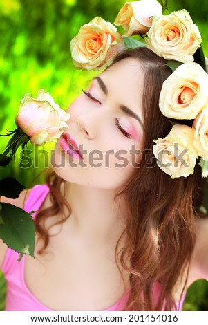 Lovely teenager girl with beautiful rose flowers in her hair