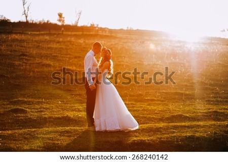 lovely wedding couple in sunset - stock photo