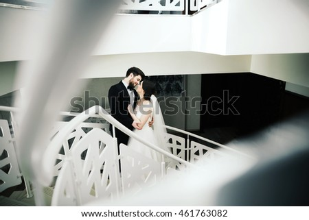 Lovely wedding photo, brunette bride and bridegroom standing together on white stairs and holding hands, portrait.