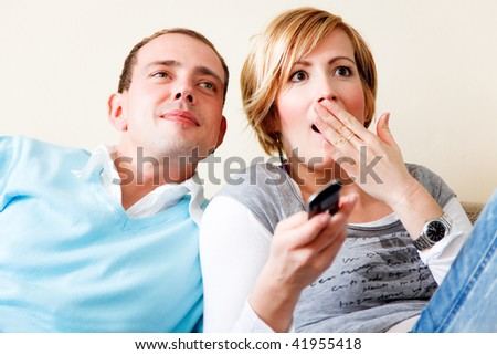 Lovely weekend couple sitting on couch watching tv while woman is shocked - stock photo