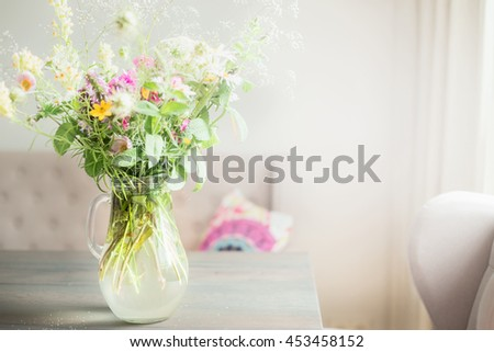 Lovely wild flowers bunch in glass vase on table in light living room , Home   decoration and interior. - stock photo