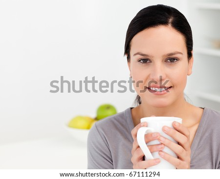 Lovely woman holding a cup of coffee while relaxing in the kitchen at home