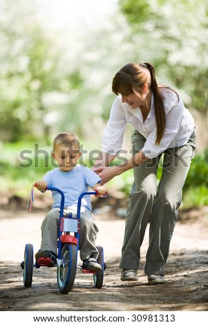 Lovely woman touching her son while he riding a bicycle in park - stock photo