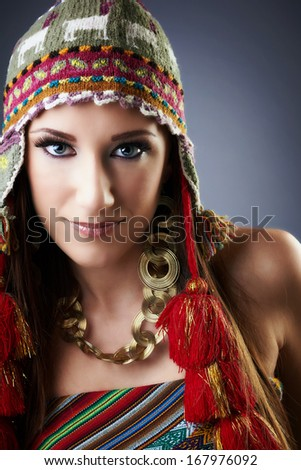 Lovely woman with beautiful blue eyes and gorgeous smile, wearing cap with tassels, golden jewelry, gray background.