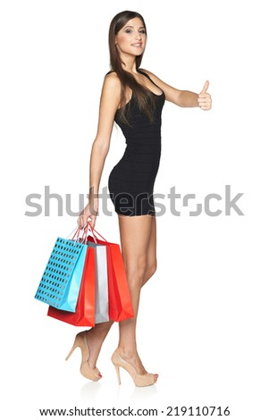 Lovely woman with shopping bags gesturing thumb up, in full length over white background - stock photo