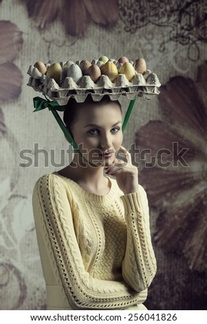lovely woman with yellow clothes posing in creative easter portrait with bizarre hat with coloured eggs in carton box - stock photo