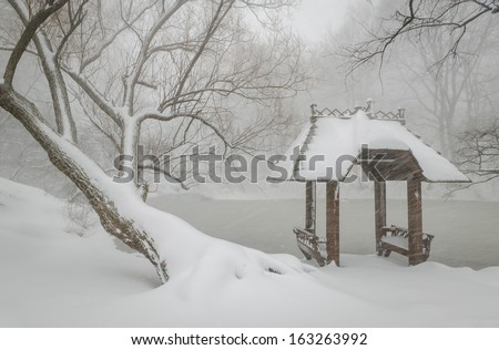 Lovely wooden shelter by the Lake during a snowfall. Gazebo and trees covered in snow by Wagner Cove. Winter peace and quiet in Central Park, New York. - stock photo