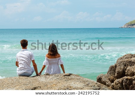 lovely young adult couple on the rocks above tropical sea, back view - stock photo