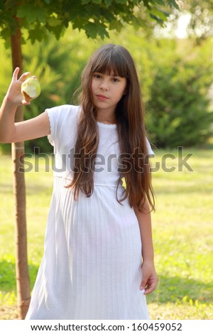 Lovely young brunette girl with a long healthy hair in a white dress eats an apple in a summer sunny day in nature