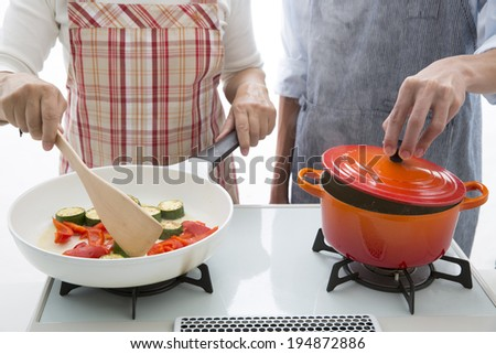 Lovely young couple cooking in the kitchen at home. Adding olive oil - stock photo