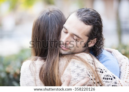 Lovely young couple hugging in a park. Love and romance concept