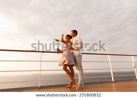 lovely young couple pointing at sea on a cruise ship at sunset - stock photo