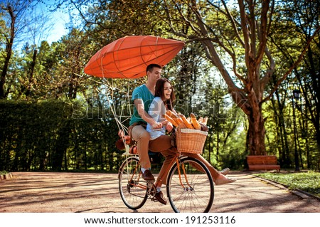 Lovely young couple riding bicycle with red dirigible and the basket full of baguettes in the park in the summer - stock photo