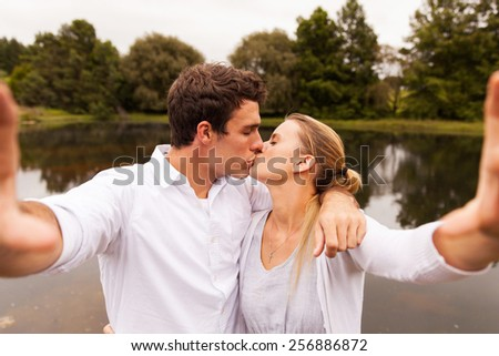 lovely young couple taking selfie kissing by the lake