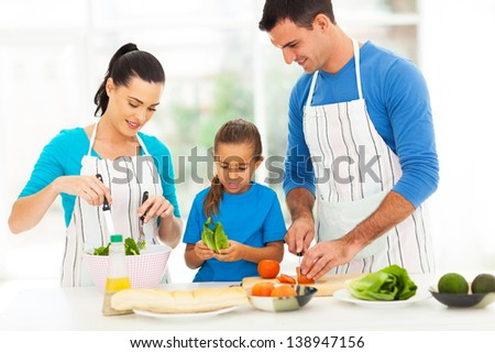 lovely young family preparing food in kitchen at home - stock photo