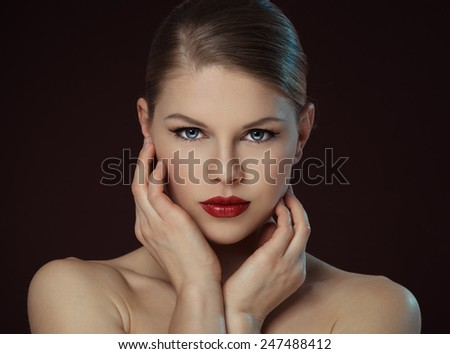 Lovely young female touching her clean face over black background. Close-up portrait of  Caucasian fashion model with professional makeup and hairstyle posing in studio.  - stock photo