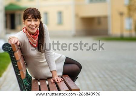 Lovely young girl relaxing on bench in city. - stock photo