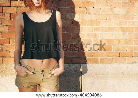 Lovely young girl wearing in a black blank T-shirt without sleeves posing against a background of a brick wall in the rays of the setting sun - stock photo