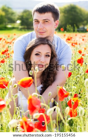Lovely young happy couple reasting on a meadow full of poppies