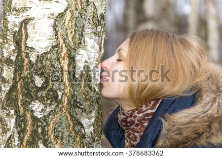 Lovely, young lady resting in a park and capturing energy of birch tree and giving thanksgiving kiss to tree