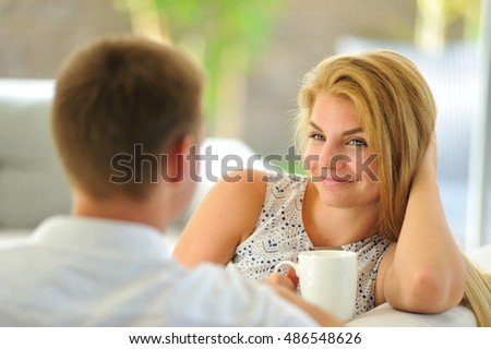 Lovely young lady sitting on a couch propped her head with one hand and holding a mug of delicious tea in another hand, in love looking at her husband