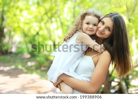 Lovely young mom and daughter in warm sunny summer day, happy family - stock photo