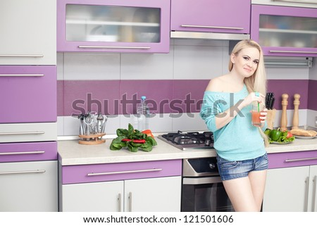 Lovely young pregnant woman enjoying fresh fruit juice in her modern kitchen. indoor shot - stock photo
