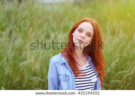 Lovely young redhead woman in a grassy field standing with her head tilted looking quizzically at the camera, upper body with copy space - stock photo