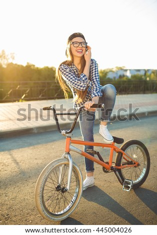 Lovely young woman in a hat riding a bicycle on city background in the sunlight outdoor. Active people - stock photo