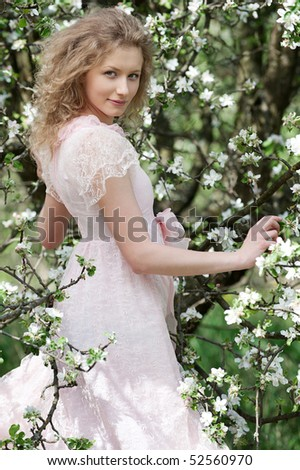 lovely young woman posing near blossoming tree