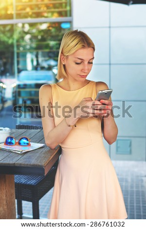 Lovely young woman sending text message with her mobile phone, charming hipster girl chatting on cell phone standing at coffee shop, female tourist connecting to wireless on telephone for navigation - stock photo